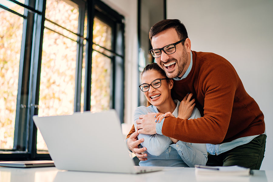 Client Center - Excited Couple Using a Laptop at Home